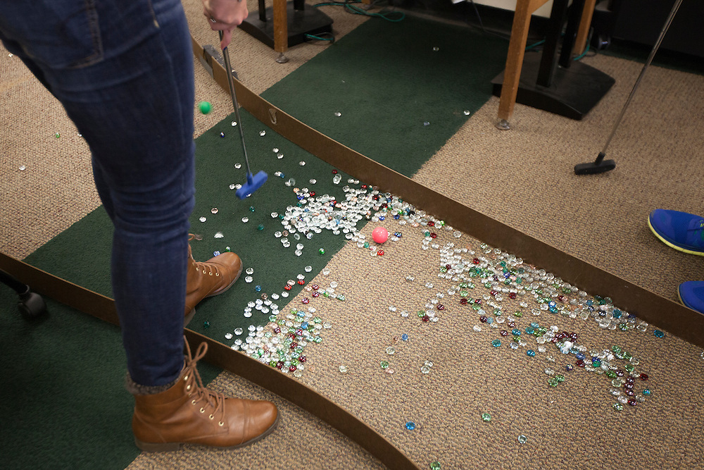 Justine Wright putts a golf ball out of a marble pit during the Alden Open, a Dad's Weekend Mini-Golf event in Alden Library, on Saturday, November 7, 2015. Photo by Kaitlin Owens