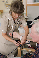 Nursing auxiliary taking patient's blood pressure on medical ward,