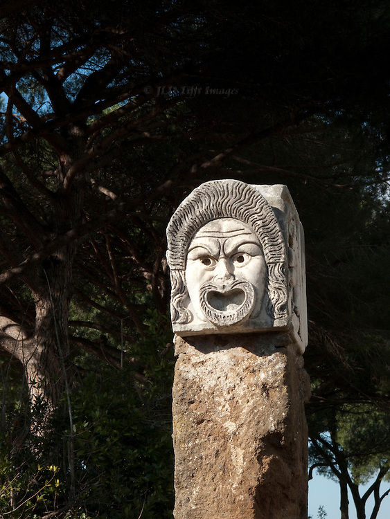 Ostia Antica. Closeup of a theatrical mask carved in stone, showing angry expression.