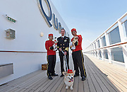 Captain Christopher Wells, center, with Queen Mary 2 Kennel Masters, poses with Ella Bean, Wally and Chloe on Cunard's remastered flaghsip, the only passenger liner to carry pets, Wednesday, July 6, 2016, at Brooklyn Cruise Terminal in New York, its U.S. homeport.  The Queen Mary 2 spent 25 days in dry dock and a refit that cost in the region of $132 million, renovating its staterooms, restaurants and public areas.  (Diane Bondareff/AP Images for Cunard)