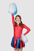 Portrait of happy young woman in cheer leader costume standing against gray background