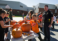 Ellie Nicolas carves a face out of her pumpkin with Officer Daniel O'Neill keeping a watchful eye as approximately 350 pumpkins are carved by Gilford Middle School students on Thursday for the Laconia Pumpkin Fest happening this weekend.  (Karen Bobotas/for the Laconia Daily Sun)