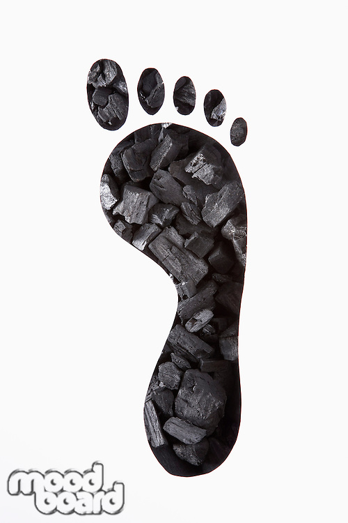 Coal seen through sheet of paper with cut shape of footprint