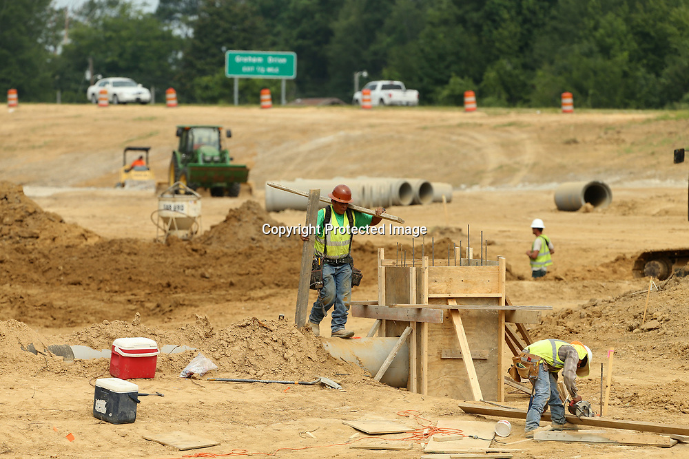 Workers build a form for concrete around a drainage pipe on South Thomas Street and Highway 76 for the on and off ramps that are under construction on Tuesday morning in Tupelo.