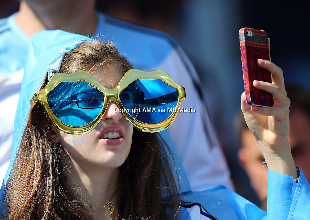 A female fan of Argentina wearing giant sunglasses takes a photo on her mobile phone