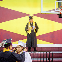 052315  Adron Gardner/Independent<br /> <br /> Tohatchi High School Cougar senior Benjamin Bia, center, reads through the ceremony program before the start of graduation in Tohatchi Friday.