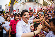 17 FEBRUARY 2013 - BANGKOK, THAILAND: Thai Prime Minister YINGLUCK SHINAWATRA accepts roses and talks to voters while campaigning for Pongsapat Pongchareon in Bangkok Sunday. Pol General Pongsapat Pongcharoen, a former deputy national police chief who also served as secretary-general of the Narcotics Control Board is the Pheu Thai Party candidate in the upcoming Bangkok governor's election. (He resigned from the police force to run for Governor.) Former Prime Minister Thaksin Shinawatra reportedly recruited Pongsapat. Most of Thailand's reputable polls have reported that Pongsapat is leading in the race and likely to defeat Sukhumbhand Paribatra, the Thai Democrats' candidate and incumbent. The loss of Bangkok would be a serious blow to the Democrats, whose base is the Bangkok area.      PHOTO BY JACK KURTZ