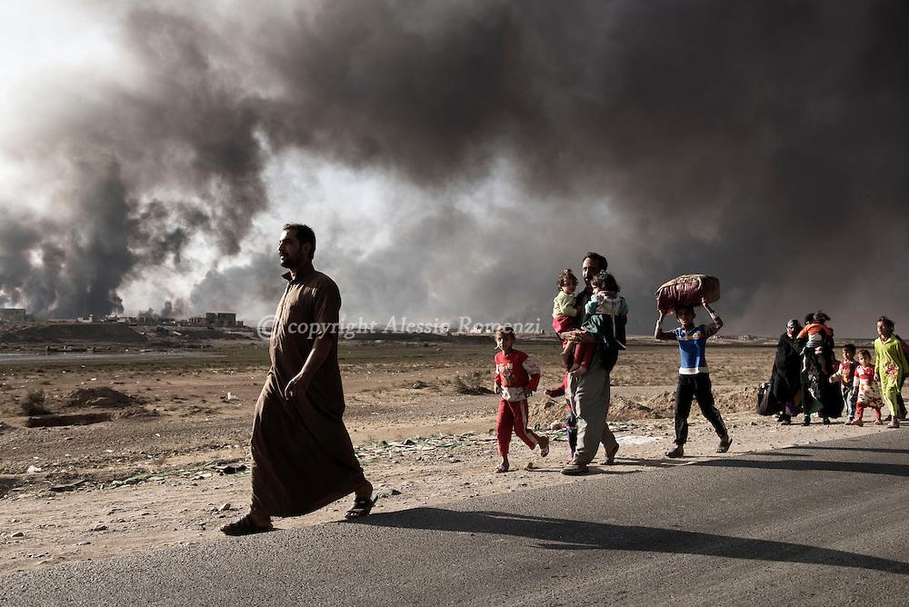 Iraq, Qarayya: Civilians fleeing by ISIS arrive at the Qayyara checkpoint.<br /> Behind them the still burning oil wells on October 31, 2016. Alessio Romenzi