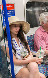 © Licensed to London News Pictures. 01/07/2015. London, UK. A woman with multiple iced drinks on a day in which commuters and tourists struggle with the intense heat on the London Underground today (01/07) on what is set to be the hottest day this decade. Photo credit : James Gourley/LNP