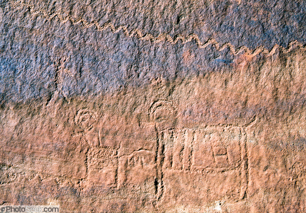 Ancient petroglyphs of bighorn sheep are chipped into the desert varnish and sandstone of Llewellyn Gulch in Glen Canyon National Recreation Area, Utah, USA.