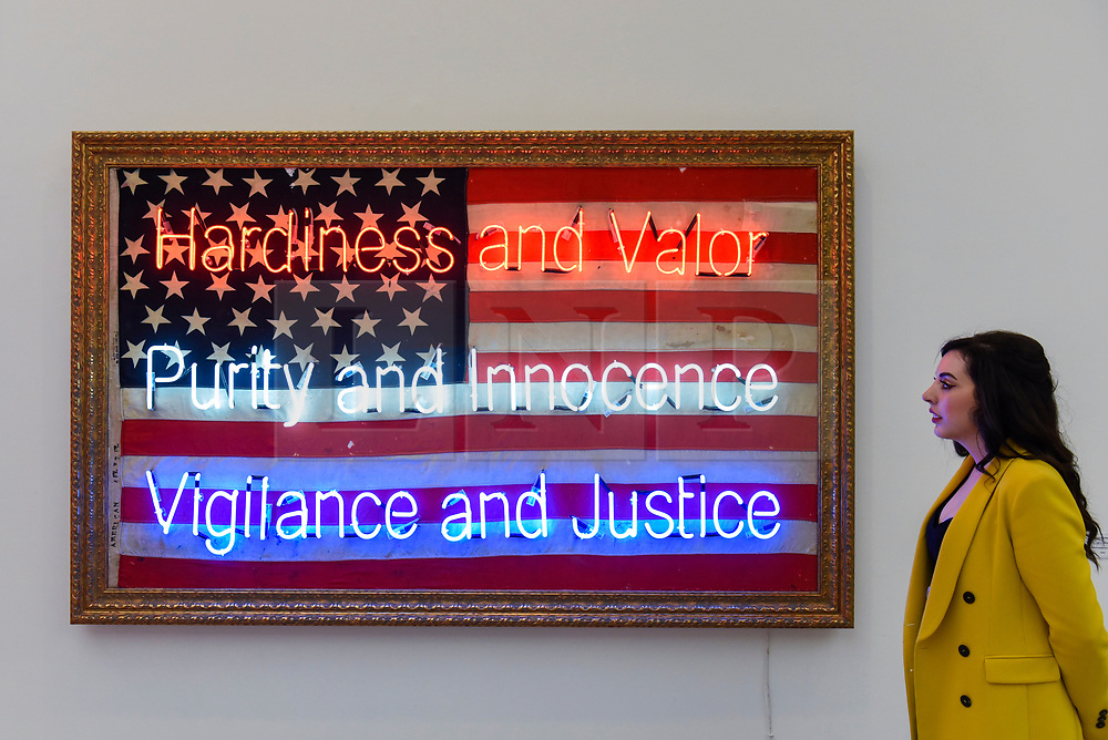 © Licensed to London News Pictures. 25/09/2019. LONDON, UK. A staff member views one of the neon works by Illuminati Neon, combining vintage flags and neon, at the preview of START, a contemporary art fair comprising eclectic works from a variety of international emerging artists.  The fair takes place at the Saatchi Gallery in Chelsea 26 to 29 September 2019.  Photo credit: Stephen Chung/LNP