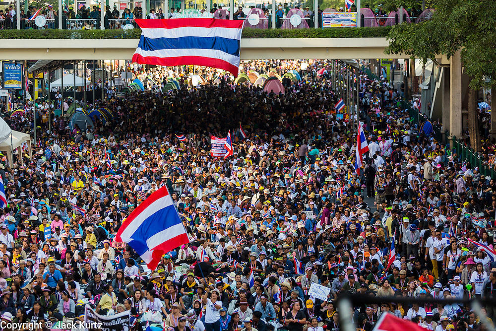 """13 JANUARY 2014 - BANGKOK, THAILAND: Anti-government protestors choke the Ratchaprasong Intersection, heart of Bangkok's high end retail shopping, during the first day of Shutdown Bangkok. Tens of thousands of Thai anti-government protestors took to the streets of Bangkok Monday to shut down the Thai capitol. The protest was called """"Shutdown Bangkok"""" and is expected to last at least a week. The Shutdown Bangkok protest is a continuation of protests that started in early November. There have been shootings almost every night at different protests sites around Bangkok, including two Sunday night, but the protests Monday were peaceful. The malls in Bangkok stayed open Monday but many other businesses closed for the day and mass transit was swamped with both protestors and people who had to use mass transit because the roads were blocked.    PHOTO BY JACK KURTZ"""
