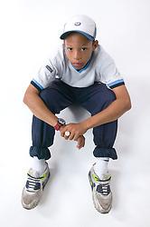Portrait of a teenaged boy sitting on the floor wearing a baseball cap,
