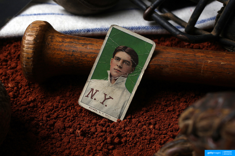 An antique vintage baseball card resting on a baseball bat. 7th June 2012. Photo Tim Clayton