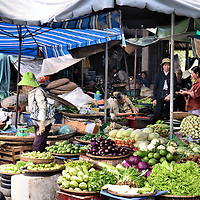 Open-air Produce or Squat Market in Hue, Vietnam<br /> Vietnamese open-air produce markets, like this one in Hue, are sometimes called a squat market because of how the women squat while cleaning and selling their vegetables. Colorful canvas and plastic tarps provide partial sun protection to both the produce vendors and their customers.