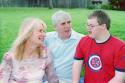 Teenage Down's Syndrome boy talking to his parents,