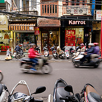 A busy street scene in Hanoi, Vietnam, reveals the buzzing motorcycle traffic and tightly packed businesses.
