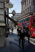 Businessmen walk past the pillars of the Bank of England through high-intensity reflected light from a nearby plate glass on Threadneedle Street in the City of London