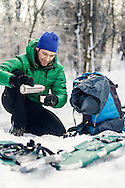 Male hiker pouring coffee on a break during a snowshoeing day trip.