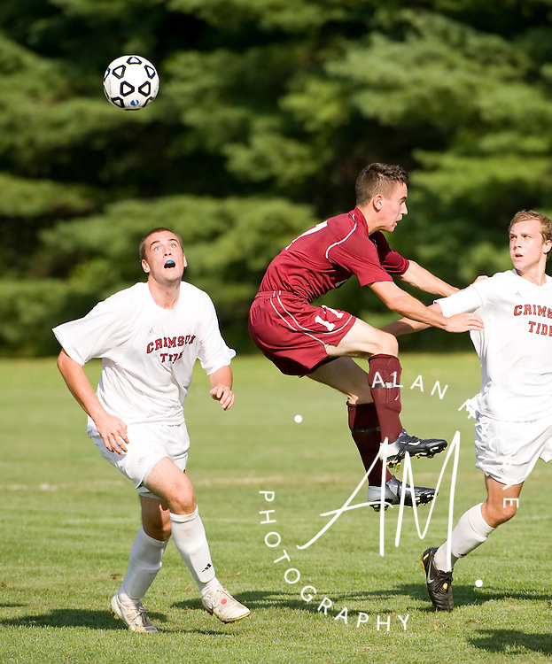 Concord's  Chad Naro looks to settle the ball after Goffstown's Josh Lafond misses the head in Friday's game at Concord's Memorial Field.  (Alan MacRae/for the Monitor)