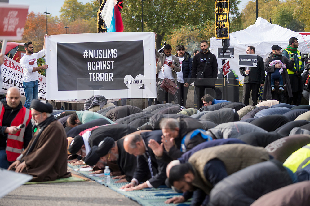 © Licensed to London News Pictures. 04/11/2018. LONDON, UK.  Members of the Muslim community pray by Marble Arch ahead of taking part in the Arbaeen Procession.  The event coincided with a multi-faith release of white doves for world peace.  Photo credit: Stephen Chung/LNP