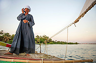 Mohammed Sayeed answers his cell phone on his felucca, while ferrying residents across the Nile River at sunset on June 22, 2013 in Assiut, Egypt. Ann Hermes/© The Christian Science Monitor 2013