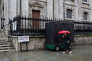 An elderly lady endures heavy rainfall on an autumn afternoon outside St. Martin-in-the-Fields church on Duncannon Street WC2, on 24th October 2019, in Westminster, London, England.