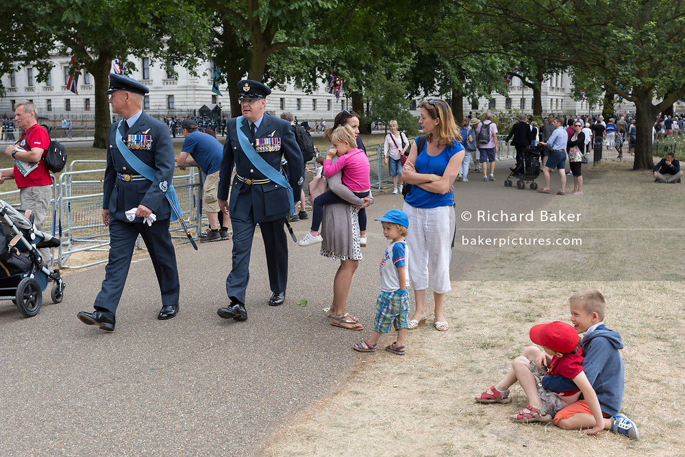 On the 100th anniversary of the Royal Air Force (RAF) and following a flypast of 100 aircraft formations representing Britain's air defence history which flew over central London, two officers walk past playing boys, on 10th July 2018, in London, England.
