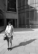 A young woman out sir a luxury shopping mall in Shanghai, with a small dog in her purse.