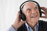 Senior man wearing head phones in studio