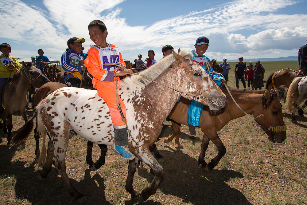 A group of young boys prepares to participate in a horse race across the Gobi Desert at the start of the Naadam Festival at the Three Camel Lodge in the Gobi Desert of Mongolia on July 31, 2012. Horse racing is one of the ?Three Manly Sports? practiced during the Naadam Festival. © 2012 Tom Turner Photography.