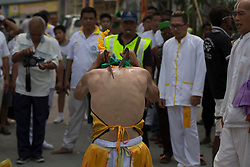 © Licensed to London News Pictures. 18/10/2015 Batu Gajah, Perak, Malaysia. A devotee in trance beats his back with swords as he prepares to come out of trance at Sam Wong Kong temple during the Nine Emperor Gods Festival celebration in Batu Gajah, Malaysia, Sunday, Oct. 18, 2015. Photo credit : Sang Tan/LNP