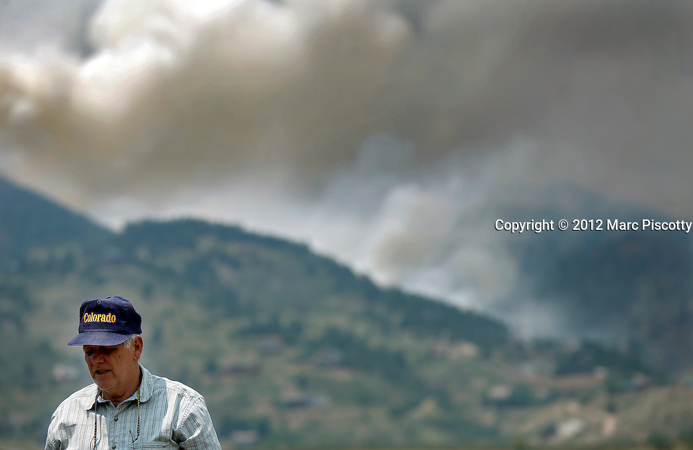 A man wearing a Colorado hat takes in the view of a ridgeline on fire during the High Park Fire on Monday June 11, 2012 near Laporte, Colorado. The High Park Fire in Larimer County has burned almost 37,000 acres and damaged or destroyed more than 100 structures. There is no containment of the fire, which is burning in the mountains about 15 miles west of Fort Collins, Co. (Photo by Marc Piscotty / © 2012)