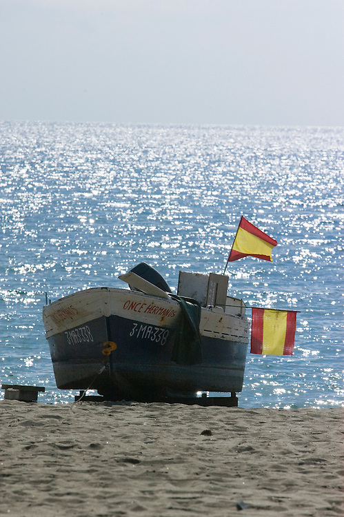 Fishing boat with two Spanish flags on the beach, Fuengirola, Costa del Sol, Spain.