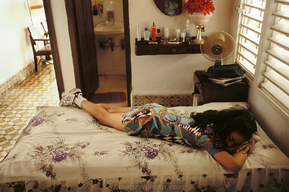 Iris Garcia Costa steals a nap after her fifteenth birthday photo shoot in various locations around Old Havana. The traditional 15th birthday coming-of-age party and whirlwind of activities for young girls is called a Quinceañera. The Costa's live in the Marianao district of Havana, Cuba.  From coverage of revisit to Material World Project family in Cuba, 2001.