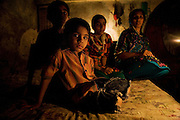 The Jamshid family sit on a bed at their home in the 'Old City' district of Lahore. ..'Load-shedding' or power outages have resulted in families resorting to small, gas powered lamps or candles for those unable to afford gas lamps...The price of candles has doubled in recent days (10Rps per candle) as demand in lieu of load shedding increases..