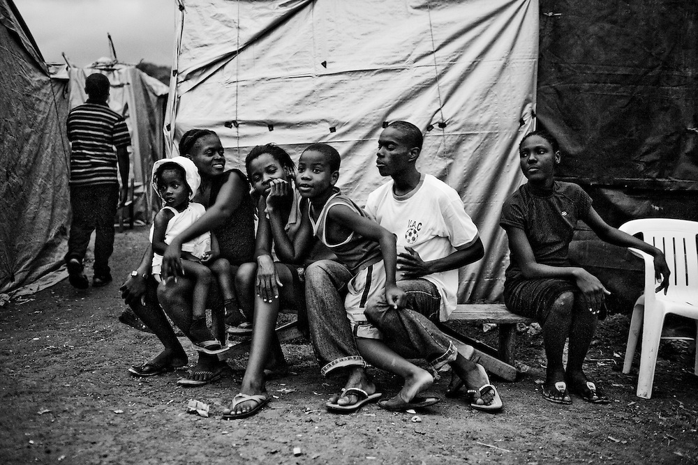 Residents of a camp for those displaced by the recent earthquake wait for an evening church service to begin in Petionville, outside Port-au-Prince, Haiti.