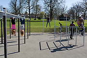 After a weekend of large numbers of Britons leaving London for holiday resorts and coastal beauty spots, and crowding into the capital's parks, the UK government is considering further restrictions of movement in public places to help social distancing during the Coronavirus pandemic. Indoor gyms are now closed but this open-air space in Ruskin Park, south London has attracted south Londoners including members of the Brixton Street Gym who exercise together in warm spring sunshine, on 23rd March 2020, in London, England.