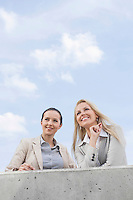 Low angle view of happy young businesswomen looking away while standing on terrace against sky