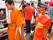 09 JULY 2011 - BANGKOK, THAILAND: Novice Buddhist monks get off a river taxi on the Chao Phraya River in the Chinatown section of Bangkok, Thailand. Chinatown is the entrepreneurial hub of Bangkok, with thousands of family owned businesses selling wholesale merchandise in everything from food like rice, peanuts and meats, to dry goods like toys and shoes.  PHOTO BY JACK KURTZ