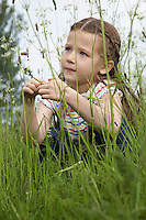 Girl (5-6) crouching in meadow