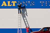JEROME A. POLLOS/Press..Chris Martin, with Yesco Coeur d'Alene, tosses a section of foam lettering Thursday from the side of the Alton's Tire building on Fourth Street in Coeur d'Alene to his coworker Jim Gaily. Alton's Tires merged with Tire-Rama Inc. last year and is now in the process of changing the signage.