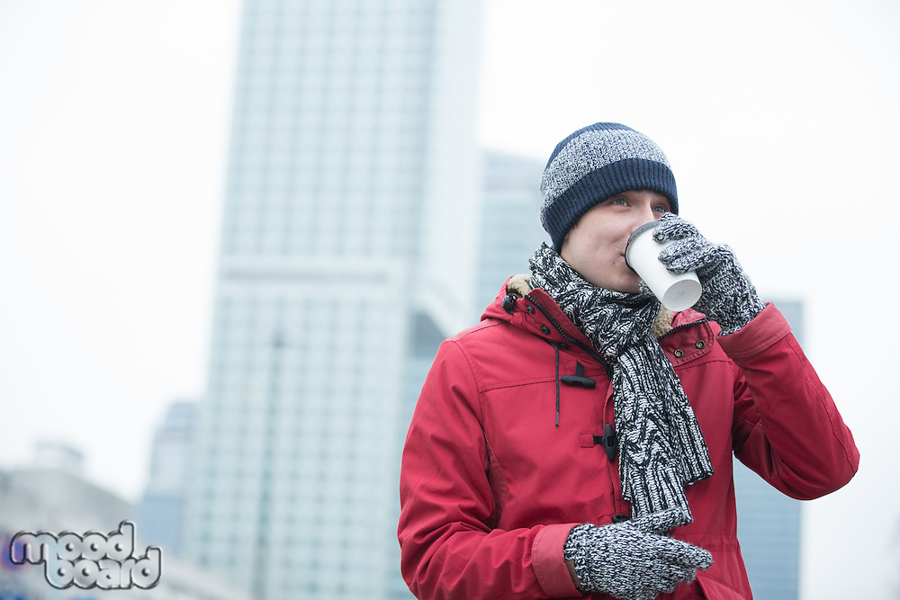 Man in warm clothing drinking coffee outdoors