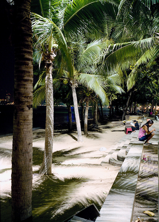 A woman sits under the palm trees at night.
