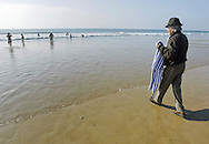 Portuguese summer. A man with a bathrobe in his hands wait for his wife to come out of the water in Carcavelos beach outskirts of Lisbon.