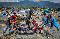 October 3, 2018 - Palu, Central Sulawesi, Indonesia - Residents try to get a motorized vehicle out of the ruins of Balaroa village after the earthquake in Palu. A deadly earthquake measuring 7.7 magnitude and the tsunami wave caused by it has destroyed the city of Palu and much of the area in Central Sulawesi. According to the officials, death toll from devastating quake and tsunami rises to 1,347, around 800 people in hospitals are seriously injured and some 62,000 people have been displaced in 24 camps around the region. (Credit Image: © Hariandi Hafid/SOPA Images via ZUMA Wire)
