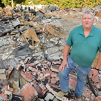Herbert Luther, pastor of Pleasant Hill Baptist Church in Ashland, stands in the ruins of the church building that burned July 19.