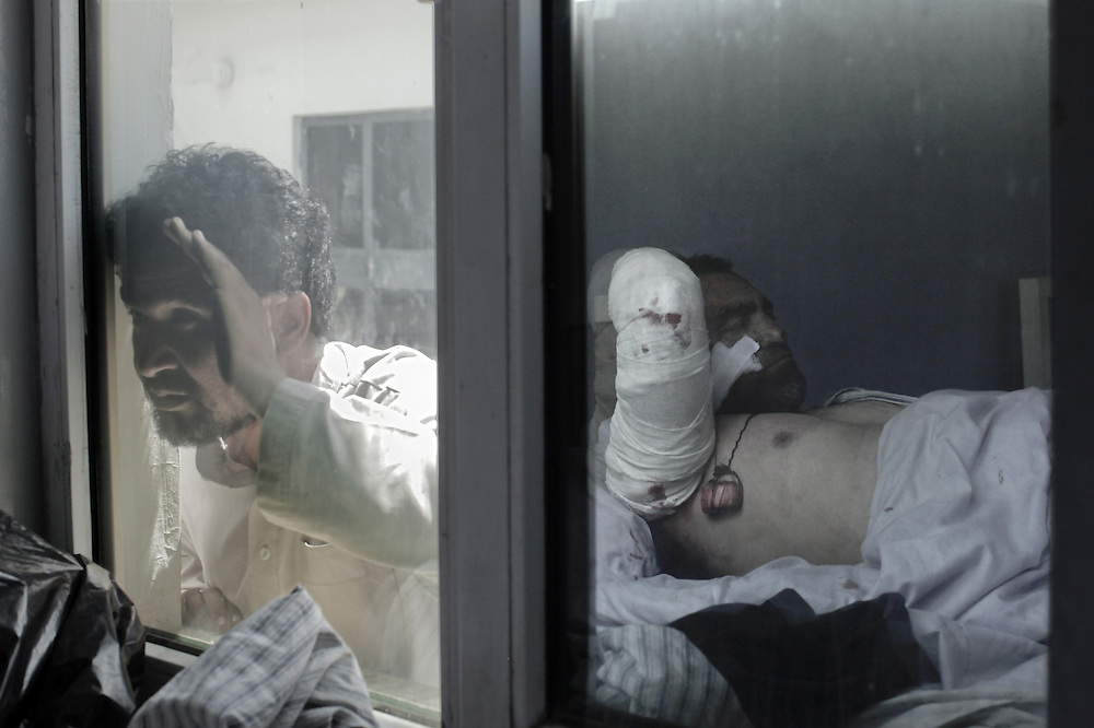 """An Afghan man (L) looks from outside towards his wounded relative in a hospital bed reflected in a window after a suicide attack in Kabul, on May 18, 2010. A suicide car bomb attack has targeted NATO troops in the Afghan capital, killing at least 20 people near parliament in the deadliest strike on Kabul in more than a year, an army doctor said. The Taliban, the militia leading a nearly nine-year insurgency against the Western-backed government and US-led foreign troops, claimed responsibility for the attack, saying they had targeted """"invading NATO forces. AFP PHOTO/Mauricio LIMA"""