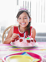 Portrait of girl (7-9) with birthday cake laughing