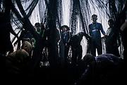 Burmese illegal migrants and fishermen cleaning their nets after off-loading the previous night's catch at a Thai fish processing factory.              Des migrants illégaux et des pêcheurs birmans nettoient leurs filets après avoir déchargé les prises de la nuit précédente dans une usine thaïlandaise de transformation du poisson.